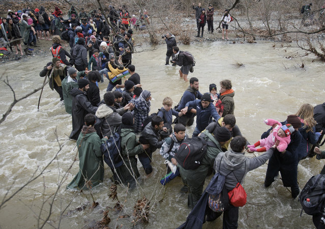 A baby is passed from hand to hand as migrants cross a river, north of Idomeni, Greece, attempting to reach Macedonia on a route that would bypass the border fence, Monday, March 14, 2016. (Photo by Vadim Ghirda/AP Photo)