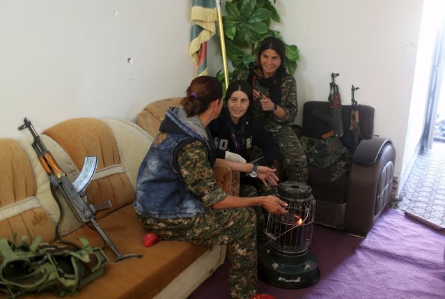 Female Kurdistan Workers Party (PKK) fighters talk as they sit around a heater at a base in Sinjar, March 11, 2015. (Photo by Asmaa Waguih/Reuters)