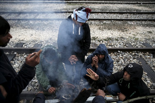 Pakistani migrants warm themselves next to a bonfire at a makeshift camp for refugees and migrants at the Greek-Macedonian border, near the village of Idomeni, Greece March 16, 2016. (Photo by Alkis Konstantinidis/Reuters)