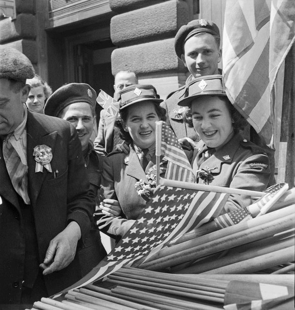 Canadian soldiers and members of the Canadian Women's Army Corps (CWAC) buy flags to wave in the VE-Day celebrations, in London May 8,1945, in this handout photo provided by Library and Archives Canada. (Photo by Sgt. Karen M. Hermeston/Reuters/Canada Department of National Defence/Library and Archives Canada)