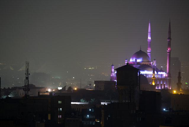 The great Mosque of Muhammad Ali Pasha in the Citadel and the great Pyramids, in rear left, are illuminated before having the light switched off to mark Earth Hour, in Cairo, Egypt, Saturday, March 19, 2016. (Photo by Amr Nabil/AP Photo)