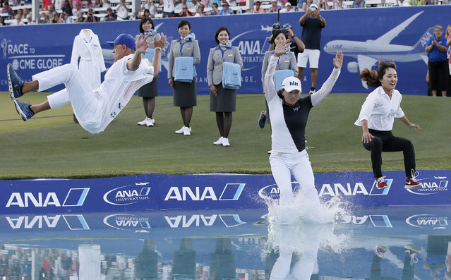 Jin Young Ko, center, of South Korea, leaps into the pond with caddie, David Brooker, left, and her agent Soo Jin Choi, right, after winning the LPGA Tour ANA Inspiration golf tournament at Mission Hills Country Club in Rancho Mirage, Calif., Sunday, April 7, 2019. (Photo by Alex Gallardo/AP Photo)