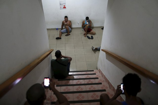 Cuban migrants look at their mobile phones inside an old hotel used as a provisional shelter in Paso Canoas, at the border with Costa Rica, in Panama March 21, 2016. (Photo by Carlos Jasso/Reuters)