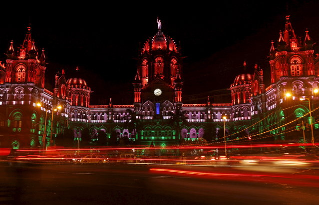 Traffic moves in front of the Chhatrapati Shivaji Terminus railway station as it is illuminated with the colours of the Indian flag in lieu of Independence Day in Mumbai, India, August 15, 2015. (Photo by Shailesh Andrade/Reuters)