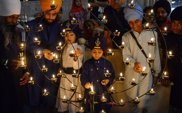 Indian Sikh devotees light candles on the occasion of the Baisakhi festival at the Golden Temple in Amritsar on April 14, 2019. Baisakhi, usually celebrated on April 13 or 14 every year, is a religious and spring festival that marks the Sikh New Year. (Photo by Narinder Nanu/AFP Photo)