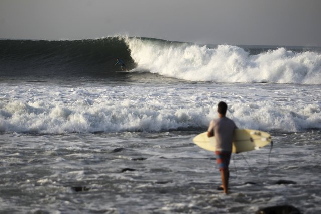 A surfer prepares to get into the water at Punta Roca Beach in La Libertad May 13, 2015. El Salvador emergency authorities has declared an orange alert along the Pacific coast due to a large swell that affected the Salvadoran coast. (Photo by Jose Cabezas/Reuters)