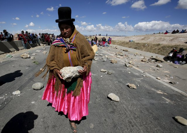 "An Aymara woman carries a rock to block a highway during a protest in ""La Apacheta"", near El Alto May 12, 2015. Protesters demand President Evo Morales' government better road connections and support for the new governor of La Paz, Felix Patzi, and his projects for their town, according to local media. (Photo by David Mercado/Reuters)"