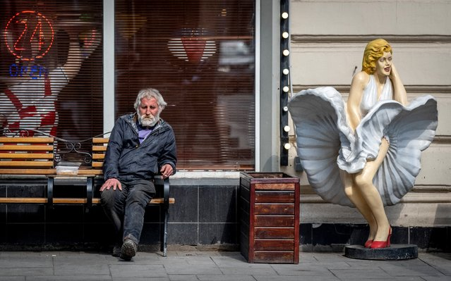 A man sits outside a cafe next to a statue of Marilyn Monroe in central Moscow on April 11, 2019. (Photo by Yuri Kadobnov/AFP Photo)