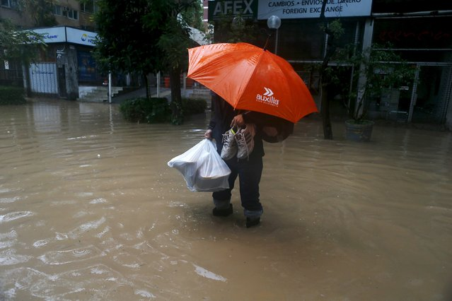 A man crosses a flooded a street in Santiago, April 17, 2016. (Photo by Ivan Alvarado/Reuters)