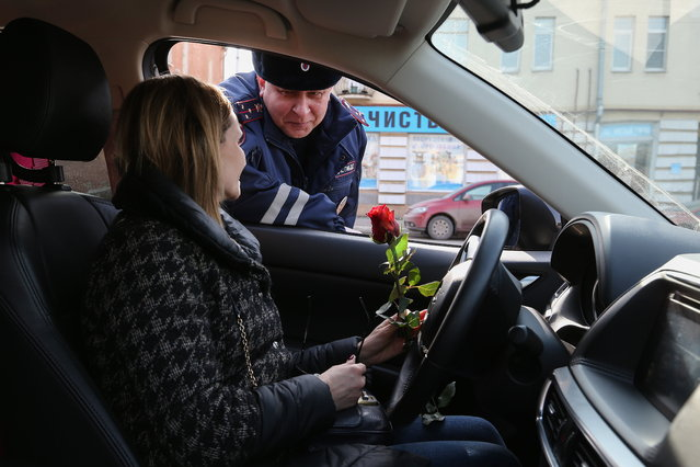 A traffic policeman congratulates a female driver on upcoming International Women's Day in Ryazan, Russia on March 7, 2017. (Photo by Alexander Ryumin/TASS via Getty Images)