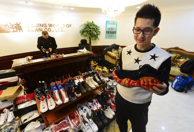 A man holds two sneakers of his collection of Nike Air Jordan as he sells them at a pawn shop in Beijing February 8, 2015. The man pawned a total of 283 pairs of his Nike Air Jordan sneakers collection for a million yuan ($160,000 USD), which he needed for the down payment of his wedding apartment. He had been collecting sneakers for over 10 years and he was planning to redeem them within the two months contract with the pawn shop, local media reported. (Photo by Reuters/Stringer)