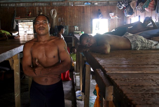 Prisoner Katokiau Maruai (L), stands next to inmates inside the sleeping dormitory of a prison located on Kiritimati Island, part of the Pacific Island nation of Kiribati, April 5, 2016. (Photo by Lincoln Feast/Reuters)