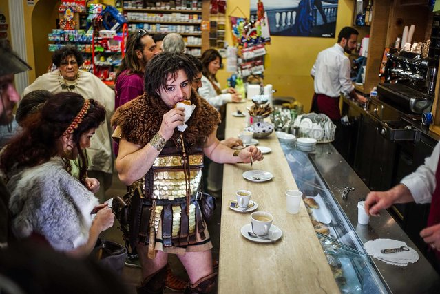 A man dressed in a traditional ancient Roman costume eats breakfast in a cafe before a parade along the ancient Roman ruins of the Colosseum, Circus Maximus and the Roman Forum to celebrate the festivities of the Christmas of Rome, on April 21, 2014. Legend says that Rome was founded by Romulus on April 21, 753 BC in an area surrounded by seven hills. (Photo by Andrew Medichini/Associated Press)