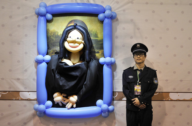 A security guard stands next to a balloon art piece depicting the painting Mona Lisa by Leonardo da Vinci at a balloon-themed carnival in Hefei, Anhui province April 26, 2014. The carnival kicked off on Saturday and will last till June 8, 2014, local media reported. (Photo by Reuters/Stringer)