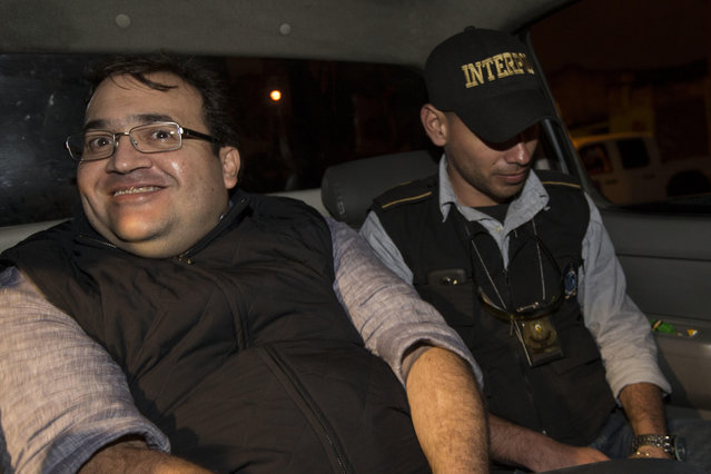 Mexico's former Veracruz state Gov. Javier Duarte, left, is escorted by an agent of the local Interpol office inside a police car as they arrive at Guatemala City, early Sunday, April 16, 2017. Duarte, who is accused of running a ring that allegedly pilfered from state coffers, has been detained in Guatemala after six months as a fugitive and a high-profile symbol of government corruption. (Photo by Moises Castillo/AP Photo)