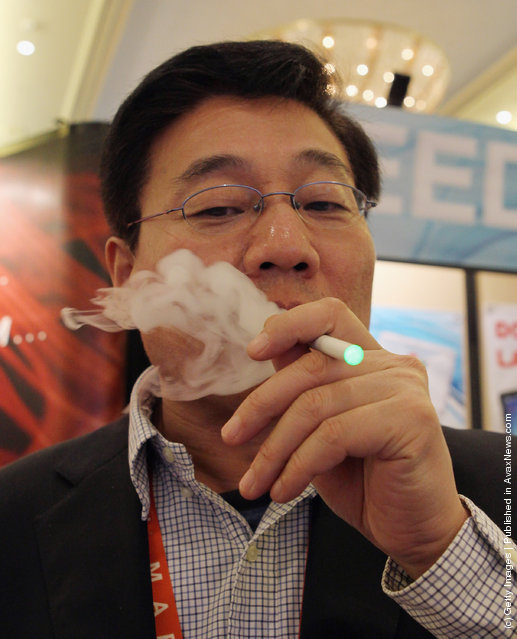 Greg Pan, CEO of Greenworld puffs away on their recently introduced electronic cigarette product which is displayed at the 2012 International Consumer Electronics Show
