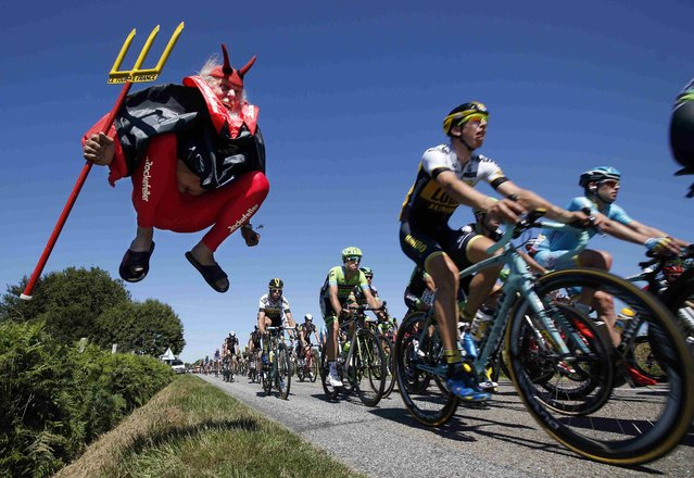 "The pack of riders make its way past Didi Senft, a cycling enthusiast better known as ""El Diablo"" (The Devil), during the 190.5-km (118.4 miles) 7th stage of the 102nd Tour de France cycling race from Livarot to Fougeres, France, July 10, 2015. (Photo by Eric Gaillard/Reuters)"