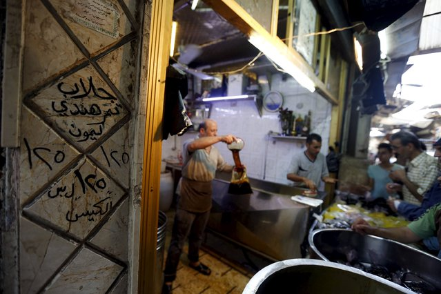 "Traditional beverages are poured into plastic bags for sale while residents wait their turn during the last week of the Muslim fasting month of Ramadan in Damascus, Syria July 11, 2015. The text on the wall reads in Arabic: ""Jallab, Tamr Hindi Lemonade, 125 Syrian Liras a bag"". (Photo by Omar Sanadiki/Reuters)"