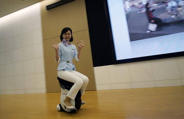 A Honda employee demonstrates the UNI-CUB personal mobility device at the carmaker headquarters' showroom in Tokyo, Japan, 13 May 2016. Honda Motor Co. said its net profit dropped by 32 per cent in fiscal year 2015 due to soaring costs generated by Takata Corp. air bags recall. (Photo by Franck Robichon/EPA)