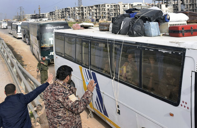 In this photo released by the Syrian official news agency SANA, Syrian government forces, left, welcome a bus carry Syrian citizens and pro-government fighters who evacuated from the two pro-government villages of Foua and Kfarya, upon their arrival at a cross point between the rebels and the Syrian government forces on the outskirts of Aleppo city, Syria, Friday, April, 21, 2017. (Photo by SANA via AP Photo)