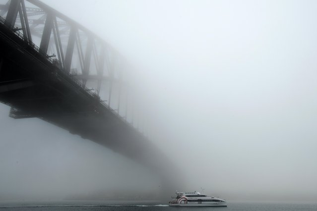 A boat passes under the Sydney Harbour Bridge during heavy morning fog in Sydney, Australia, 07 July 2019. (Photo by Joel Carrett/EPA/EFE)