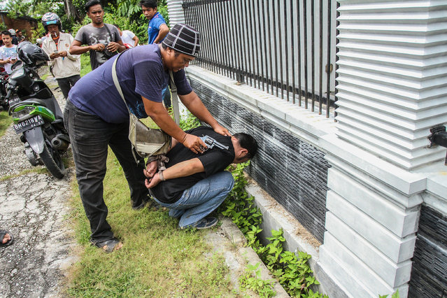 A plain-clothed police officer arrests an inmate who escaped from Sialang Bungkuk Prison in Pekanbaru, Riau province, Indonesia, 05 May 2017. According to media reports, hundreds of inmates escaped from an overcrowded prison in Pekanbaru and triggered a massive security search operation. (Photo by Rony Muharrman/EPA)