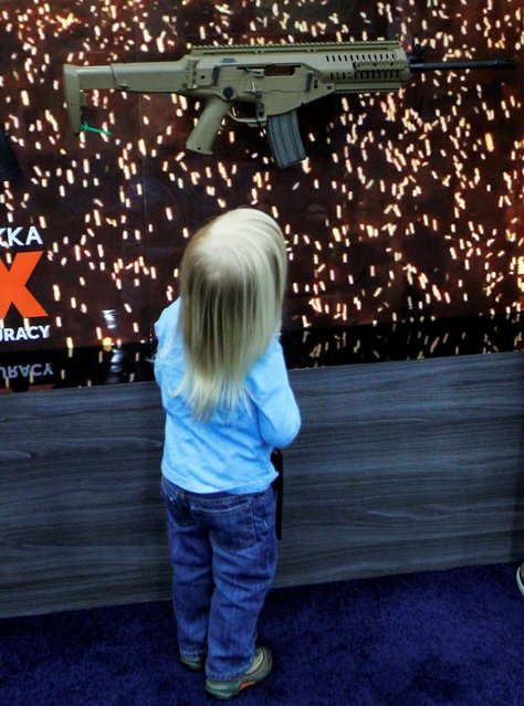 A young child looks over a gun on the exhibit floor at the National Rifle Association's annual meetings & exhibits show in Louisville, Kentucky, May 21, 2016. (Photo by John Sommers II/Reuters)