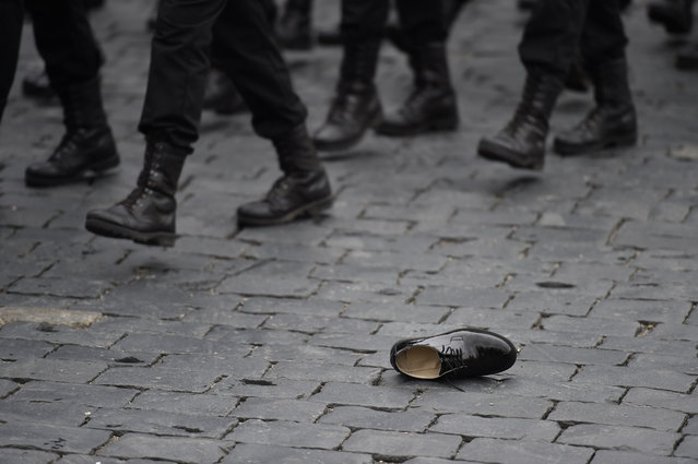 A shoe lies on paving stones as servicemen march during the Victory Day military parade at Red Square in Moscow on May 9, 2017. (Photo by Natalia Kolesnikova/AFP Photo)