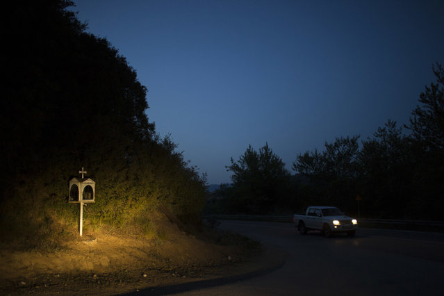 In this photo taken on Thursday, April 27, 2017, a car drives near an iron roadside shrine near the village of Avrami, in the Peloponnese region of southern Greece. (Photo by Petros Giannakouris/AP Photo)