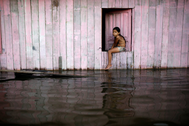 A child is seen on a street flooded by the rising Rio Solimoes, one of the two main branches of the Amazon River, in Anama, Amazonas state, Brazil on June 24, 2019. (Photo by Bruno Kelly/Reuters)