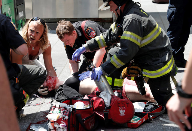 An injured woman is helped by emergency workers as she lies on the sidewalk in Times Square after a speeding vehicle struck pedestrians on the sidewalk in New York City, U.S., May 18, 2017. (Photo by Mike Segar/Reuters)