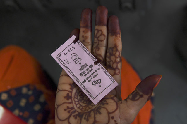 A woman travelling on a Delhi Transport Corporation bus shows a pink ticket in New Delhi on October 29, 2019, allowing her to a free ride following a Delhi goverment travel scheme distributing free bus tickets for women safety and empowerment. India's national capital on October 29 rolled out a scheme to make public transport free for women, authorities said. (Photo by Sajjad Hussain/AFP Photo)