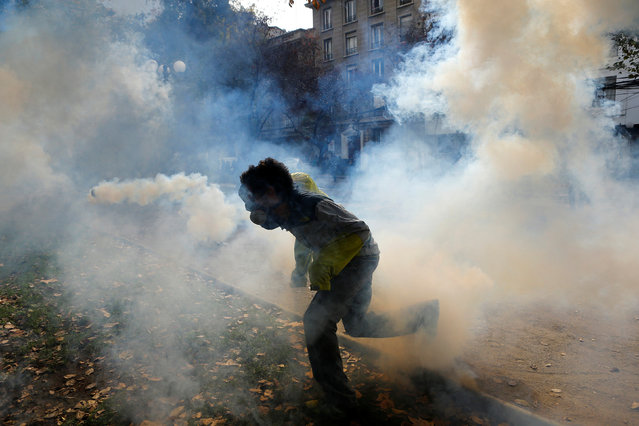 A demonstrator runs through a tear gas cloud as they clash with riot police during an unauthorized march called by secondary students to protest against government education reforms in Santiago, Chile, May 26, 2016. (Photo by Ivan Alvarado/Reuters)