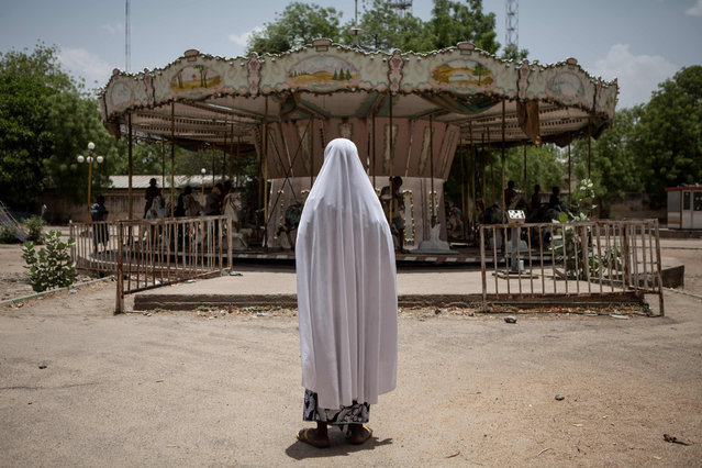 A girl watches other children playing on a merry-go-round in an abandoned amusement park in Maiduguri, Nigeria, on April 27, 2017. In Maiduguri, where the population has doubled to over two million as a result of Boko Haram insurgency, thousands of children are homeless. (Photo by Florian Plaucheur/AFP Photo)