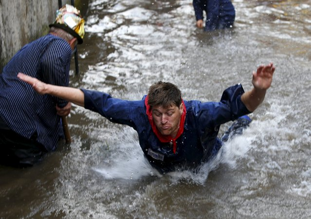 Fisherman Stefan Albrecht reacts after catching a trout in a small river while celebrating Fischertag (Fisherman's Day) in downtown Memmingen, southern Germany, July 25, 2015. (Photo by Michaela Rehle/Reuters)