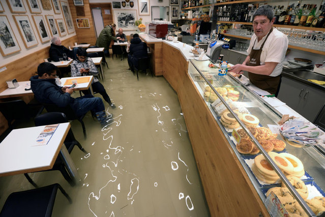 Venetian people sit in a flooded bar amid rising water levels in Venice, northern Italy, 17 November 2019. High tidal waters returned to Venice on Saturday, four days after the city experienced its worst flooding in more than 50 years. (Photo by Andrea Merola/EPA/EFE)