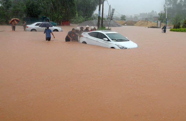 Rescuers try to move a car trapped on a flooded street in Qinzhou, southwest China's Guangxi province on June 11, 2014. Strong storms hit areas of the Guangxi region, leaving Qinzhou municipality heavily flooded, local media reported. (Photo by AFP Photo)