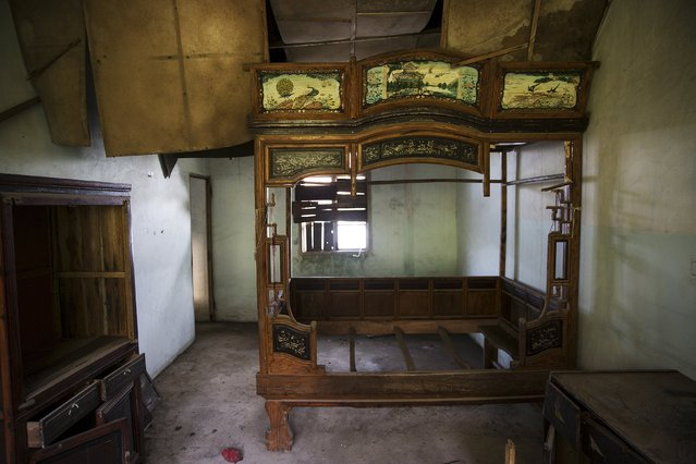 A bed and other furniture are left inside a room of a small apartment at the abandoned fishing village of Houtouwan on the island of Shengshan July 26, 2015. (Photo by Damir Sagolj/Reuters)
