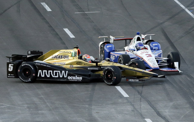 James Hinchcliffe (5) collides with Helio Castroneves (3), of Brazil, on pit road after a pit stop early in the IndyCar auto race at Texas Motor Speedway, Saturday, June 10, 2017, in Fort Worth, Texas. (Photo by Tony Gutierrez/AP Photo)