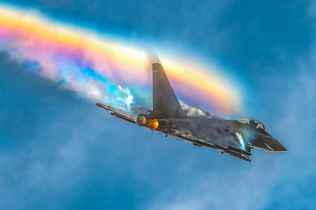 A Typhoon jet flown by Flt Lt Jim Peterson practising over RAF Coningsby in the East Lindsey district of Lincolnshire, England on September 27, 2019 producing a rainbow effect over the plane. The rainbow is made of crystalized or frozen water vapor that reflect and refract sunlight, causing the rainbow effect. (Photo by Claire Hartley/Bav Media)