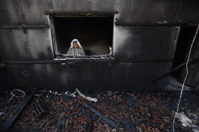 A Palestinian man inspects a house after it was torched in a suspected attack by Jewish settlers killing an 18-month-old  Palestinian child, his four-year-old brother and parents were wounded, according to a Palestinian official from the Nablus area. at Duma village near the West Bank city of Nablus, Friday, July 31, 2015. (Photo by Majdi Mohammed/AP Photo)