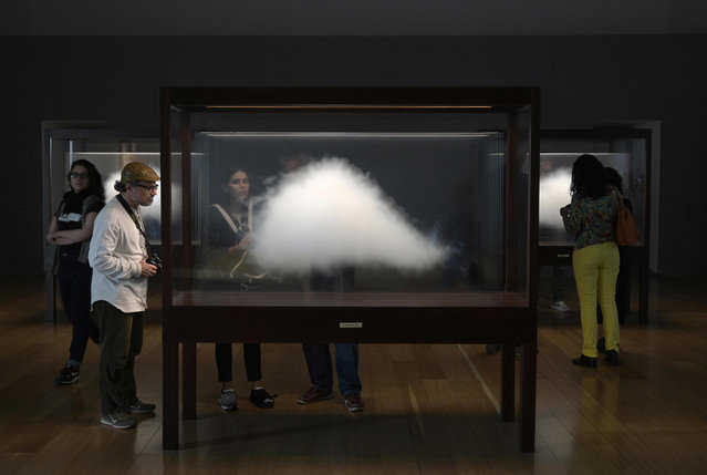 """People watch Argentine conceptual artist Leandro Erlich's installation """"Clouds"""" of his exhibition entitled """"Liminal"""" at the Museum of Latin American Art (MALBA) in Buenos Aires on October 18, 2019. The popularity of Erlich, 46, is such that some call him """"The Messi of Argentinian art"""". His works, which could be a magic trick or an illusion, become viral in social networks and mark records of visits. His most monumental work – a sand traffic jam in real size – will be unveiled next week in Miami during the Art Basel. (Photo by Juan Mabromata/AFP Photo)"""