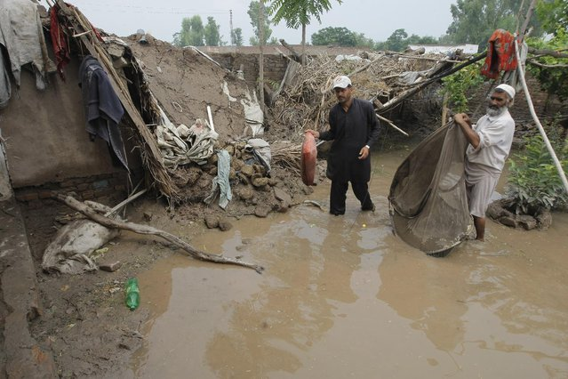 Pakistans collect their belongings from their houses destroyed by flooding in Peshawar, Pakistan, Monday, August 3, 2015. (Photo by Mohammad Sajjad/AP Photo)