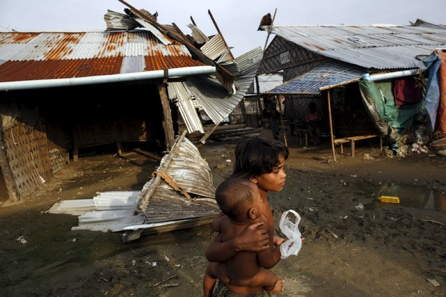 Rohingya girls pass in front of a damaged shelter in Rohingya IDP camp outside Sitttwe, Rakhine state August 4, 2015. (Photo by Soe Zeya Tun/Reuters)