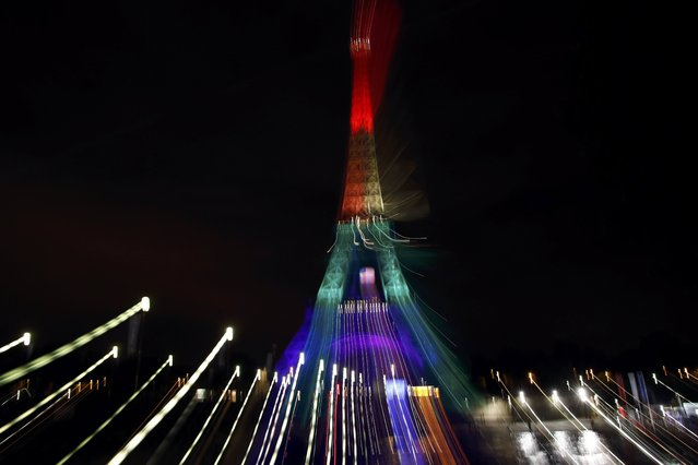 The Eiffel Tower is illuminated in memory of the victims of the gay nightclub mass shooting in Orlando, in Paris, France, June 13, 2016. Picture taken with long exposure and a zoom lens. (Photo by Gonzalo Fuentes/Reuters)