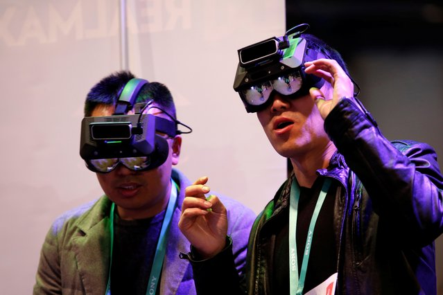 Attendees try out RealMax augmented reality headsets during the 2020 CES in Las Vegas, Nevada, U.S. January 8, 2020. (Photo by Steve Marcus/Reuters)