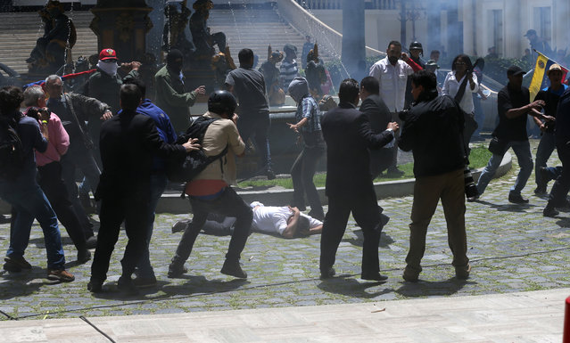 Pro-government militias attack opposition lawmakers during a special session coinciding with Venezuela's independence day, in Caracas, Wednesday, July 5, 2017. The attack, in plain view of national guardsmen assigned to protect the legislature, comes amid three months of often-violent confrontations between security forces and protesters who accuse the government of trying to establish a dictatorship by jailing foes, pushing aside the opposition-controlled legislature and rewriting the constitution to avoid fair elections. (Photo by Fernando Llano/AP Photo)