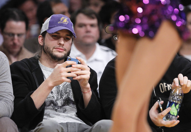 Ashton Kutcher looks at his phone as the Lakers play the Rockets in Los Angeles, January 2012. (Photo by Lucy Nicholson/Reuters)