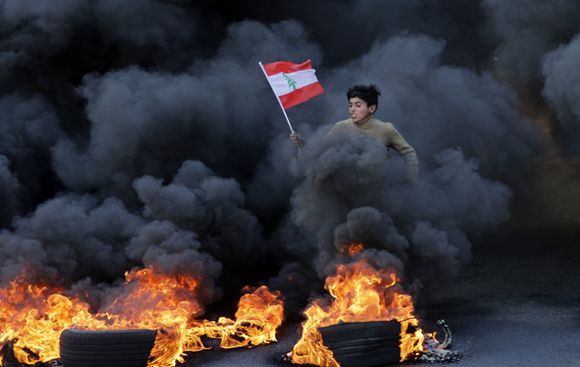 "A Lebanese youth runs with a national flag as smoke billows from burning tires during a demonstration in Jal el-Dib area on the northern outskirts of the Lebanese capital Beirut on January 14, 2020. Lebanese protesters resumed blocking major highways in what they said would be a ""week of wrath"" demanding an end to a nearly three-month political vacuum. Although protests had declined in size in recent weeks, demonstrations have been ongoing since October, increasingly targeting banks and state institutions blamed for driving the country towards collapse. (Photo by Joseph Eid/AFP Photo)"