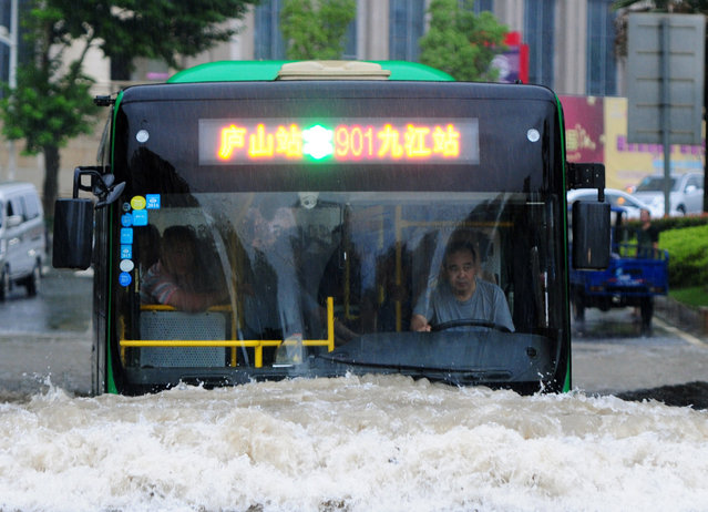 A bus goes through a flooded area in Jiujiang, Jiangxi Province, China, June 19, 2016. (Photo by Reuters/China Daily)